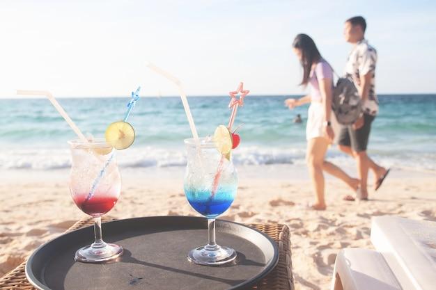 ビーチを歩く恋人たちとの夏の飲み物