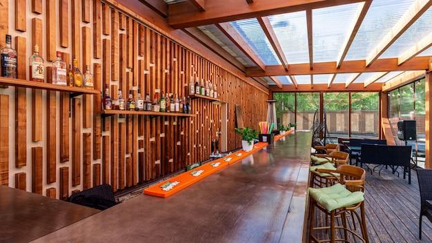 Летнее пустое уличное кафе в парке. бар с современным дизайном, деревянные стены, высокие барные стулья