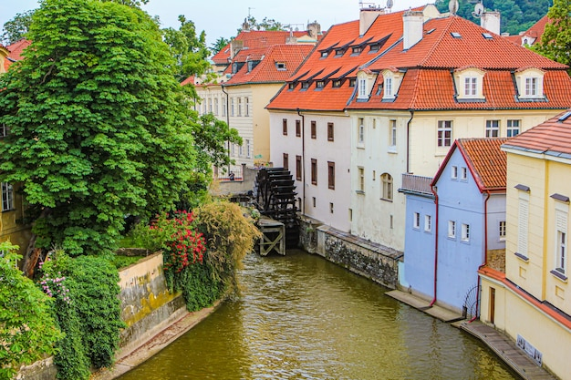 Summer european city. view of a cozy courtyard. river channel and water mill