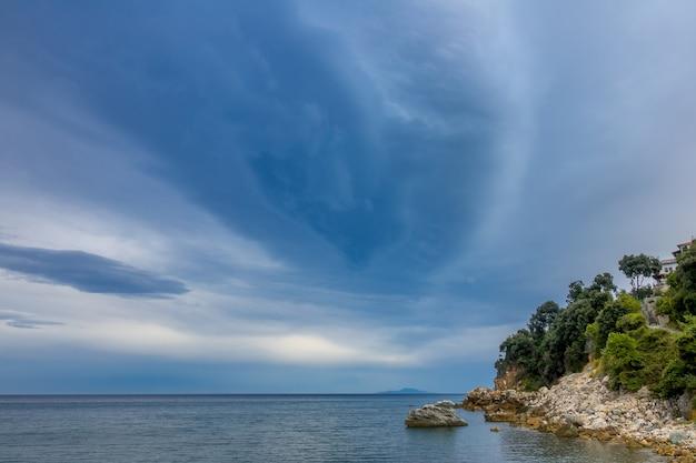 小さな岩のビーチでの夏の夜。丘の上の木々に囲まれた穏やかな海と石造りの建物