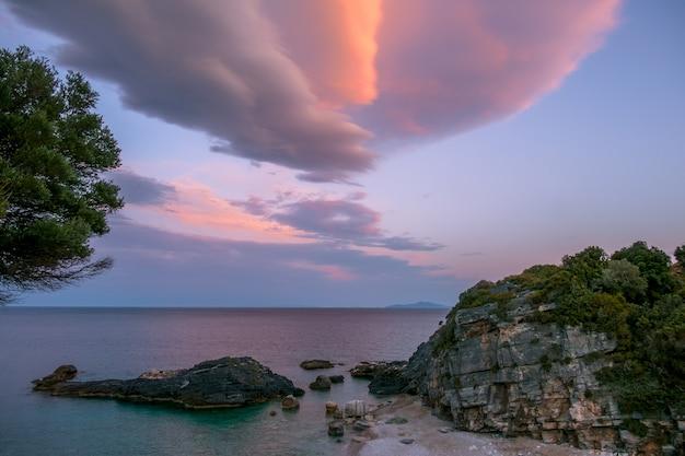 小さな岩のビーチでの夏の夜。多色の雲