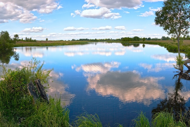 Панорама озера летнего вечера бурная с отражениями облаков.
