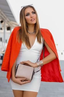 夏のファッションルック。海辺の近くでポーズをとる赤いジャケットと白いドレスの魅惑的なブロンドの女性。