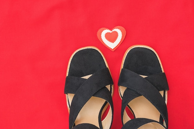 Summer fashion black women's shoes on red fabric with red heart.