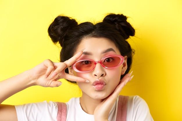 여름 패션 개념. 선글라스에 귀 엽 고 매력적인 아시아 소녀, v-sign kawaii를 표시 하 고 노란색에 서있는 카메라를보고.