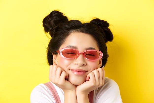 여름 패션 개념. 낭만적 인 얼굴 표정으로 꿈꾸는 아시아 소녀, 공상 또는 선글라스를 착용하고 닫힌 눈과 행복한 미소로 아름다운 것을 이미징합니다.