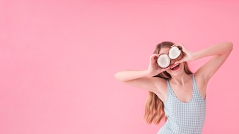 Summer fashion concept with woman holding coconut in front of eyes