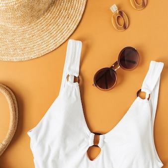 Концепция летней моды с женским купальником и аксессуарами на имбирной поверхности