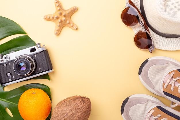 Летняя мода плоская планировка. ветки монстеры, солнцезащитные очки, кроссовки, шляпа и ретро-камера