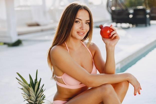 夏のファッション。果物を持つ女性。休暇中の女の子。