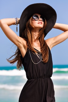 Summer fashion portrait of beautiful woman enjoy windy sunny day near ocean, vacation style. young stylish girl wearing black romper vintage hat and big sunglasses, bright colors, freedom, happiness