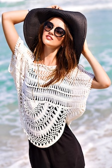 Summer fashion portrait of beautiful woman enjoy windy sunny day near ocean, vacation style. young stylish girl wearing black romper vintage hat and big sunglasses, bright colors
