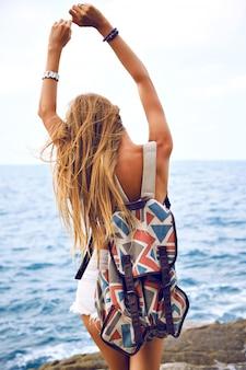 Il ritratto di moda di estate va giovane donna che viaggia con lo zaino nel periodo estivo, in posa vicino all'oceano al giorno di pioggia, vento triste umore.
