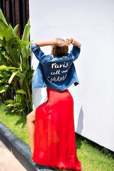 夏のファッションの肖像画o熱帯の国の外でポーズをとる、エレガントな高級ドレスと流行のデニムジャケットを着て、踊り、楽しんでいる見事なエレガントなファッションの女の子。