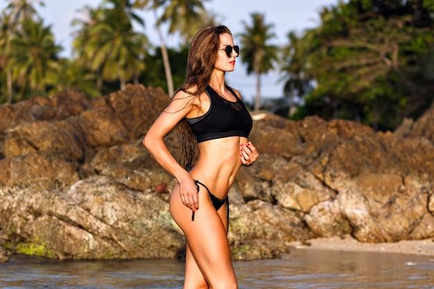 해변에서 포즈를 취하는 예쁜 여자의 여름 패션 초상화, 젖은 패션 모양, 맞는 몸매, 검은 색 비키니, 슬림 한 피트니스 몸
