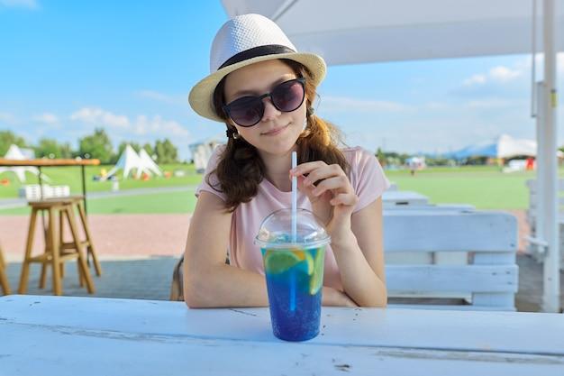 さわやかなベリーカクテルと屋外カフェに座っているサングラス帽子の10代の少女の夏のファッションの肖像画。