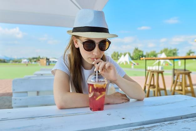 屋外カフェに座っているサングラスの帽子のティーンエイジャーの夏のファッションの肖像画