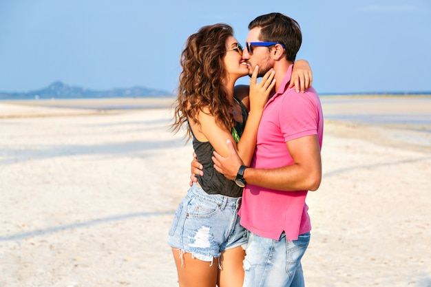 Летняя мода портрет молодой довольно стильной пары хипстеров в влюбленных объятиях и позирующих на удивительном пляже острова, весело проводящих время в одиночестве, в яркой повседневной одежде и солнцезащитных очках.