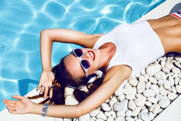 Летний модный портрет молодой сексуальной девушки ди-джея, лежащей возле бассейна, в сексуальных мини-шортах со звездами, винтажными солнцезащитными очками, милой прической и ярким макияжем, слушающей музыку в наушниках.