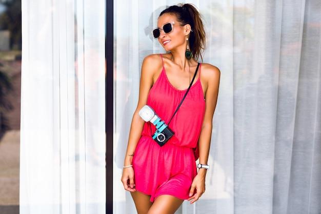 Летняя мода портрет молодой женщины, позирующей, улыбаясь и весело, носить неоновый стильный комбинезон и солнцезащитные очки, держа забавную ретро-камеру.