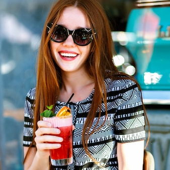 Summer fashion portrait of pretty young elegant ginger woman, sitting at terrace , drinking tasty lemonade, glamour outfit, sunny vacation, relax, joy, natural beauty.