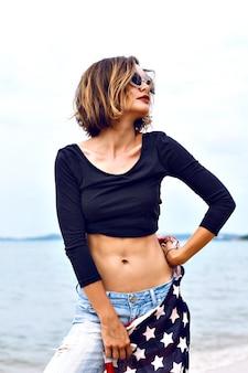 Ritratto di moda estiva di donna sexy in forma sbalorditiva, che indossa jeans e top corto, che tiene la bandiera americana, trascorre del tempo in spiaggia in una giornata piovosa.