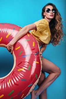 Summer fashion portrait of stylish beautiful woman with float