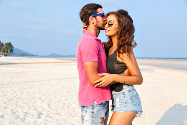 Summer fashion portrait of young pretty stylish hipsters couple in love hugs and posing at amazing island beach, having fun alone, wearing bright casual clothes and sunglasses.