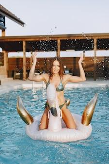 夏のファッション。プールの近くの水着の女性。休暇中の女性。