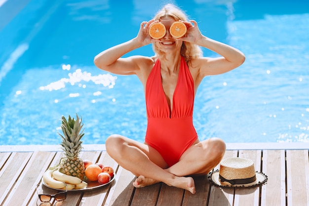 夏のファッション。プールの近くの赤い水着の女性。果物を持つ女性。