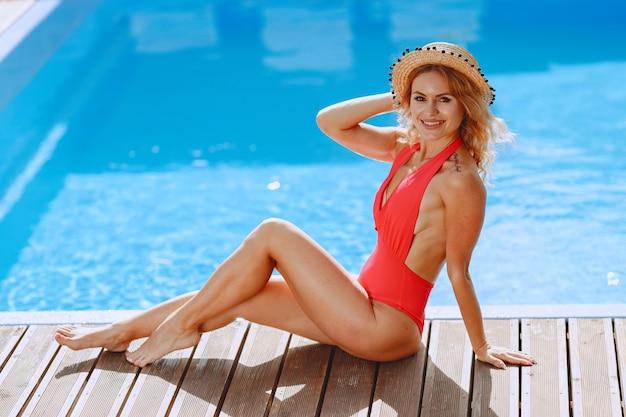夏のファッション。プールの近くの赤い水着の女性。