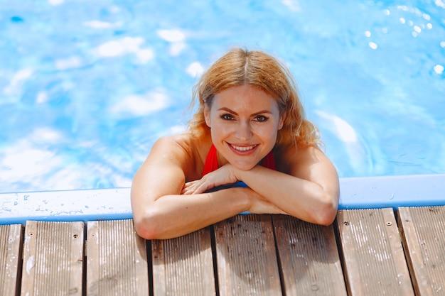 Moda estiva. donna in costume da bagno rosso vicino alla piscina.