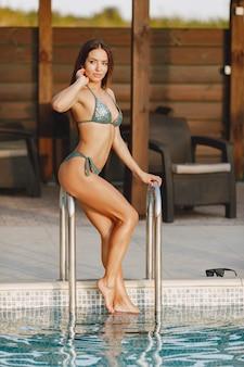 Moda estiva. donna in costume da bagno vicino alla piscina. signora in vacanza.