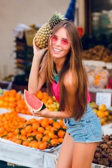 夏のファッショナブルな女の子はアナナスとトロピカルフルーツマーケットでスイカのスライスでポーズをとってください。