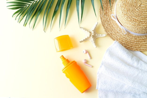 Summer female beach accessories flat lay top view. sun hat, sunscreen bottle, palm leaf, starfish, towel and earphone with copy space