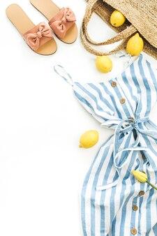 夏の女性ファッションのスタイリッシュな構成。白い背景にドレス、スリッパ、ストロー、レモン、チューリップの花、アクセサリー。フラットレイ、トップビュー