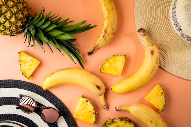 Summer female fashion, travel accessories, top view of tropical fruits - peach background. flat lay