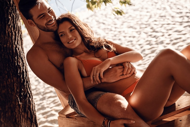 Summer filled with joy.  beautiful young couple embracing and smiling while resting on the river shore