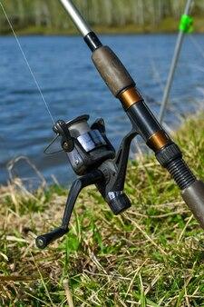 호수에서 여름 낚시입니다. 강 낚시 도구입니다. 릴이 있는 낚싯대의 클로즈업.