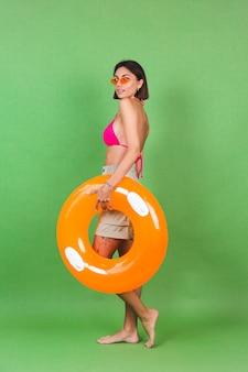 ピンクのビキニと明るいオレンジ色の膨脹可能なリング ラウンドとサングラスの緑のサングラス、幸せな陽気な興奮した陽気な肯定的な夏に合うスポーティな女性