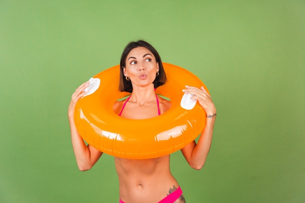 Летняя спортивная женщина в розовом бикини и ярко-оранжевом надувном кольце на зеленом, счастливая, веселая, взволнованная, радостная, позитивная.