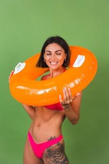 Donna sportiva in forma estiva in bikini rosa e anello gonfiabile arancione brillante rotondo su verde, felice allegro eccitato gioioso positivo