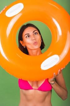 Donna sportiva in forma estiva in bikini rosa e anello gonfiabile arancione brillante rotondo su verde, allegra giocosa con smorfie divertenti funny