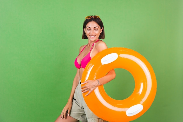 Summer fit sporty woman in pink bikini and bright orange inflatable ring round and sunglasses on green, happy cheerful excited joyful positive