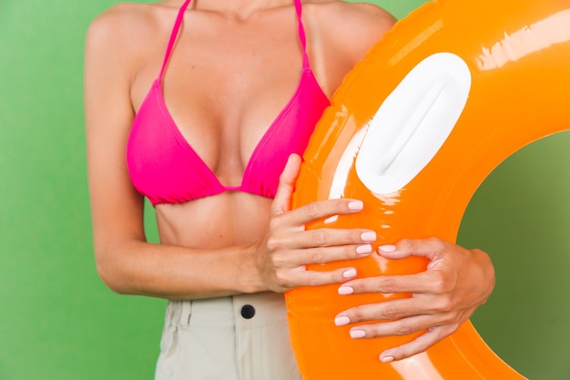 Summer fit sporty woman in pink bikini and bright orange inflatable ring round and sunglasses on green, no head shot
