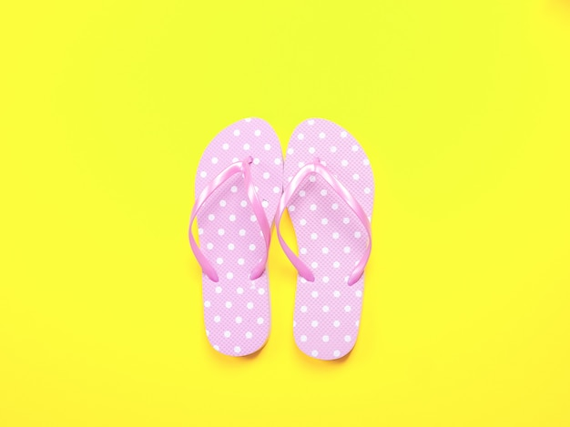 Summer flat lay. beach accessories pink flip flops and sunglasses on yellow background.