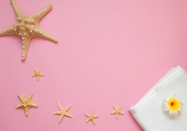 夏フラットレイアウトの概念。ピンクの背景の海の星。コピースペースを持つ夏のトップビューのコンセプト。