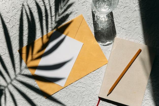 夏のフラットは、コンクリートの背景に横たわっていたメモ帳の桃と環境に優しいメッシュのショッピングバッグ