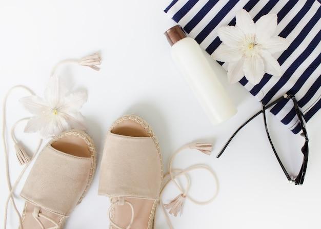 Летние плоские летние сандалии, солнцезащитные очки с белыми цветами и творческий фон с видом на белую бутылку