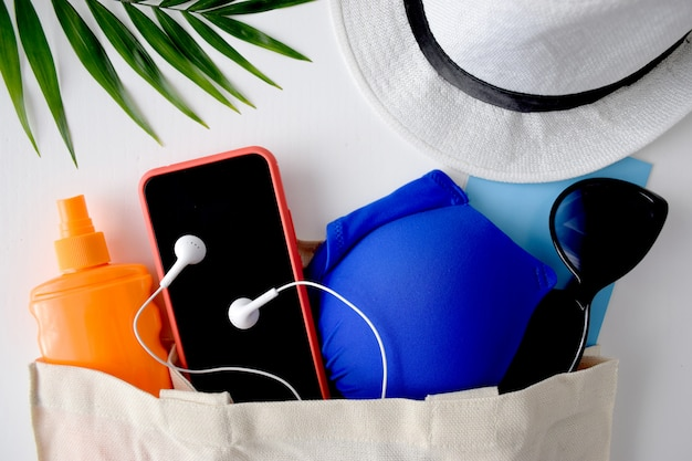 Summer flat lay traveller accessories, palm leaf, hat, sunglasses, phone, sunscreen, headphones